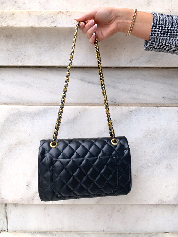 Black quilted faux leather shoulder bag with gold hardware detailing and chain strap with back pocket