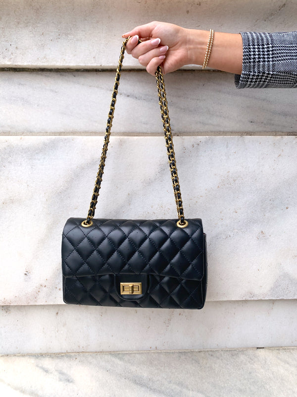 Black quilted faux leather shoulder bag with gold hardware detailing and chain strap