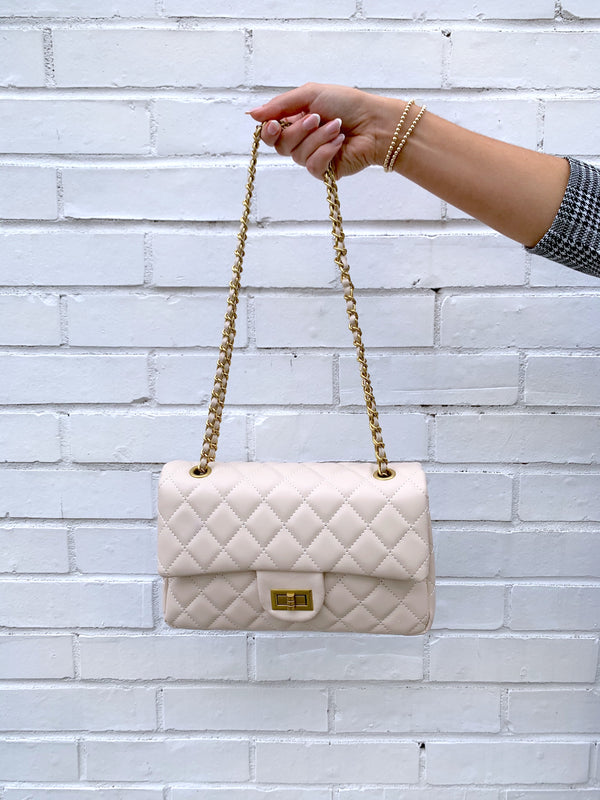 Cream quilted faux leather shoulder bag with gold hardware detailing and chain strap