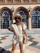 V-neck beige kimono short sleeve romper with front waist tie with straw hat and straw crossbody bag
