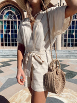 V-neck beige kimono short sleeve romper with front waist tie and mini straw bag