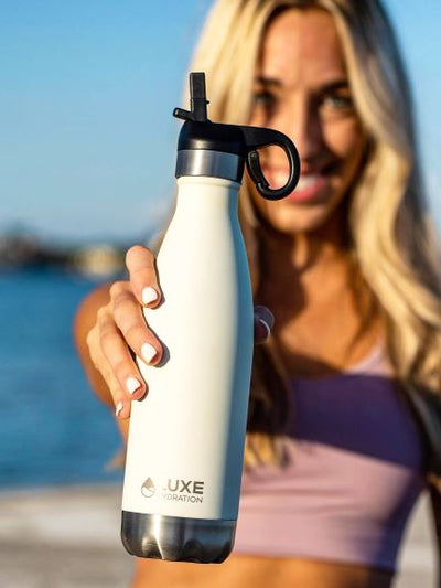 Woman holding a 17oz stainless steel water bottle with Sport Cap attached