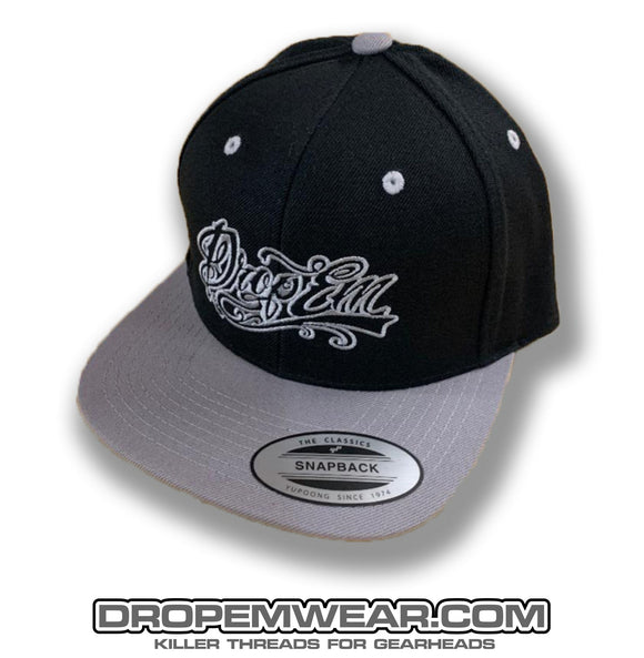BLACK FLAT BILL SNAP BACK WITH GREY BILL AND GREY TATTOO SCRIPT LOGO
