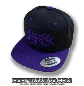 BLACK FLAT BILL SNAP BACK WITH PURPLE BILL AND PURPLE TATTOO SCRIPT LOGO