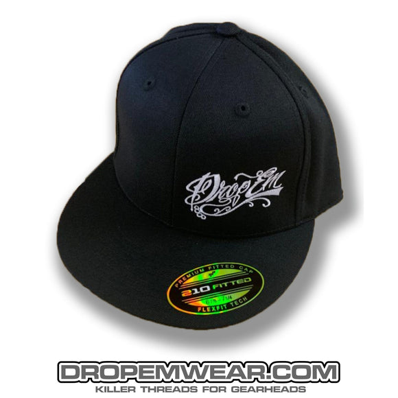 BLACK FLAT BILL FLEX FIT HAT WITH WHITE SCRIPT LOGO ON LEFT PANEL