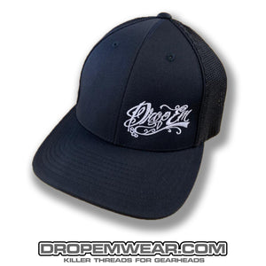 PACIFIC HEADWEAR CURVED BILL FITTED TRUCKER HAT BLACK/BLACK WITH WHITE TATTOO SCRIPT LOGO ON LEFT PANEL