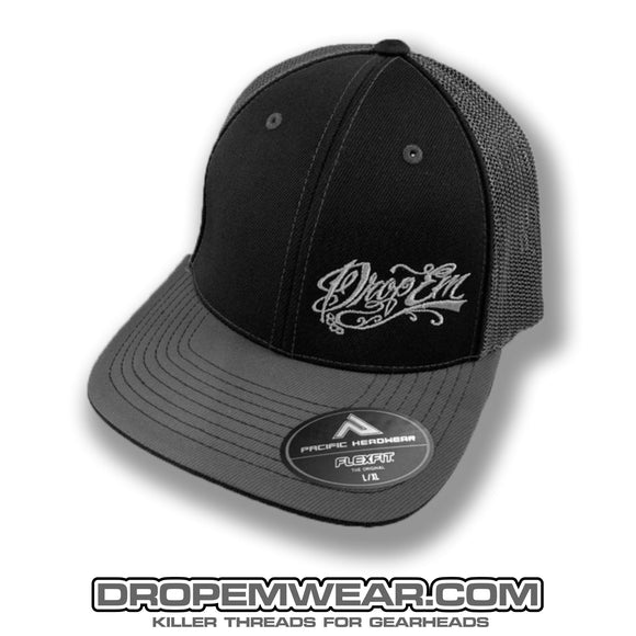 PACIFIC HEADWEAR CURVED BILL FITTED TRUCKER HAT BLACK/GRAPHITE WITH TATTOO SCRIPT LOGO ON LEFT PANEL