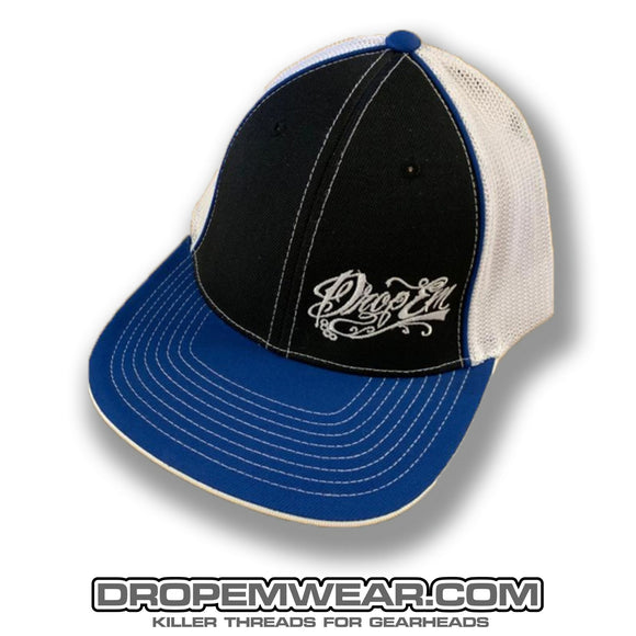 PACIFIC HEADWEAR CURVED BILL FITTED TRUCKER HAT BLUE/BLACK/WHITE WITH TATTOO SCRIPT LOGO ON LEFT PANEL