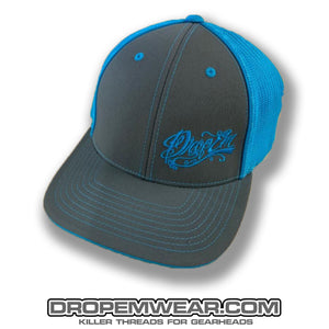 PACIFIC HEADWEAR CURVED BILL FITTED TRUCKER HAT NEON BLUE/GRAPHITE WITH TATTOO SCRIPT LOGO ON LEFT PANEL
