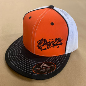 PACIFIC HEADWEAR FLAT BILL FITTED TRUCKER HAT BLACK/ORANGE/WHITE WITH TATTOO SCRIPT LOGO ON LEFT PANEL