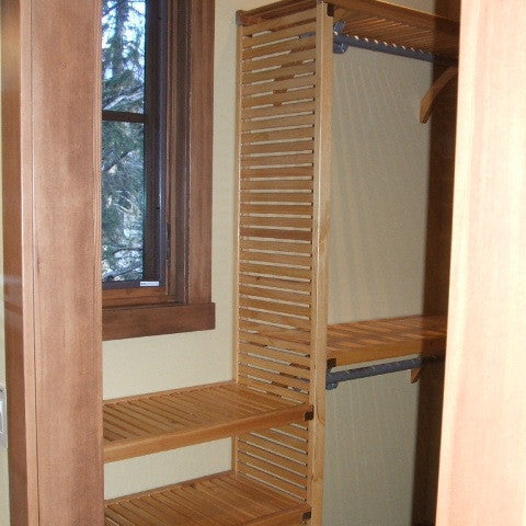 John Louis Home solid wood shelving custom closet design accommodating a window.