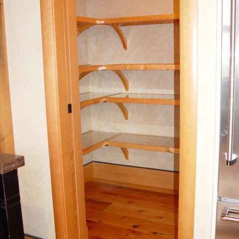 Honey maple John Louis Home closet solid wood shelving design in L-shaped kitchen pantry.