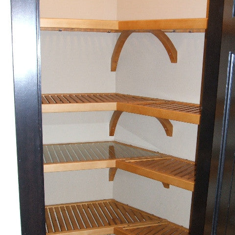 Honey Maple John Louis Home closet solid wood shelving design in L-shaped kitchen pantry with angled sidewalls.
