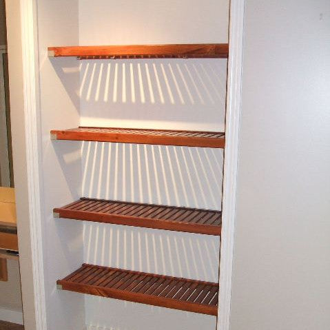 Four levels of Red Mahogany John Louis Home closet solid wood shelving design in linen closet.