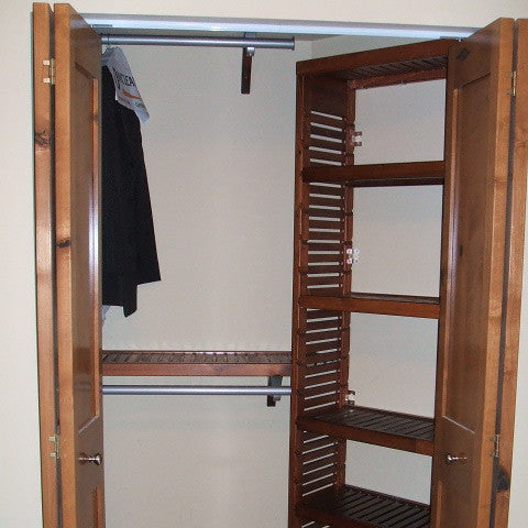 John Louis Home solid wood shelving design with tower mounted on angled wall in bedroom closet.