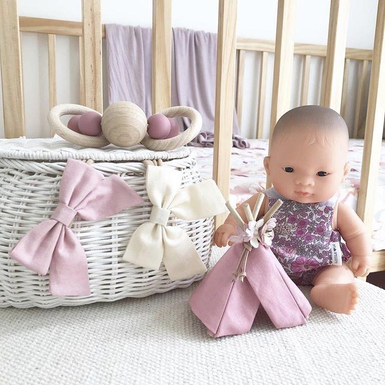 Miniland Asian Baby Doll next to rattan basket
