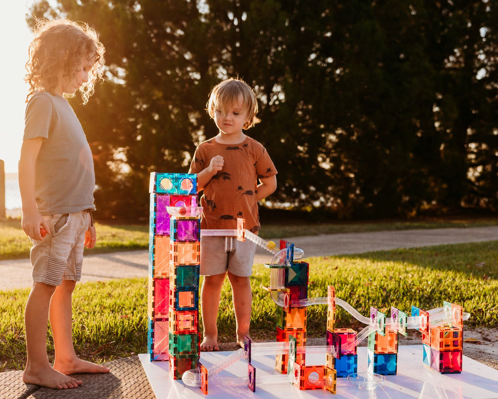 Connetix marble run outdoors with sun shining and kids playing