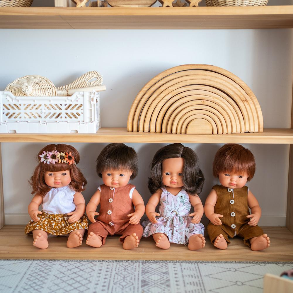 Miniland Doll collection of brunette and red haired baby dolls on wooden playshelf