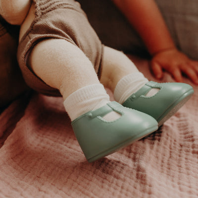 Dinkum Doll shown wearing basil green slip on shoes