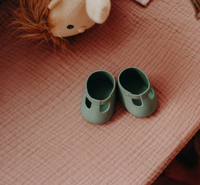 Dinkum Doll slip on shoes in Basil Green from Olli Ella with Dinkum Doll head popping out