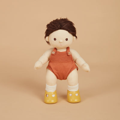 Dinkum Doll from Olli Ella wearing rust romper and corn yellow slip on doll's shoes