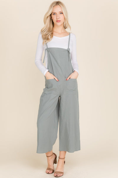 Sage colored adjustable jumpsuit with front pockets and a white tshirt underneath.
