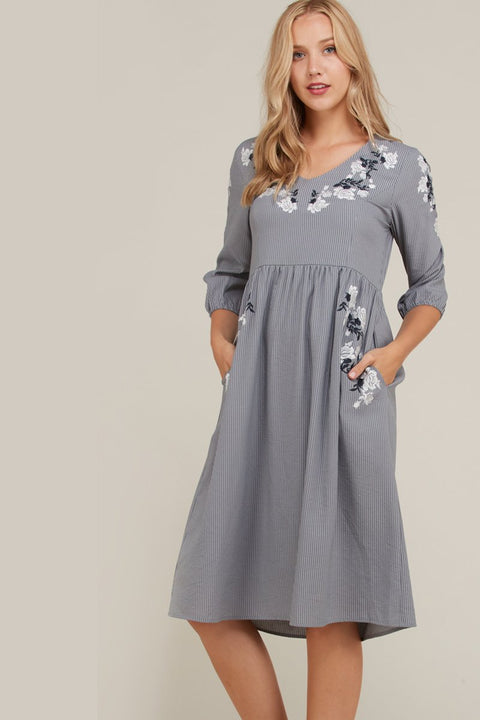 Grey striped dress with pockets and front floral embroidery.