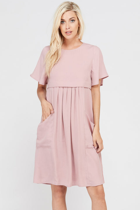 Nursing friendly blush colored babydoll dress with front pockets.