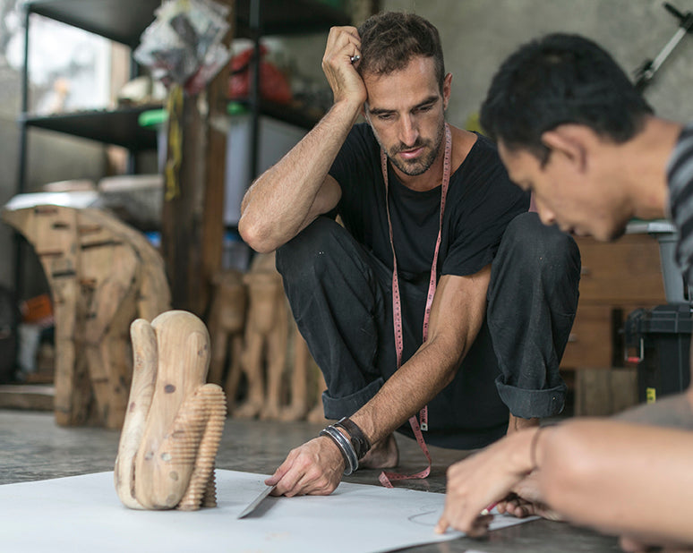 Two men sitting on the floor over a pattern and a wooden sculpture designing