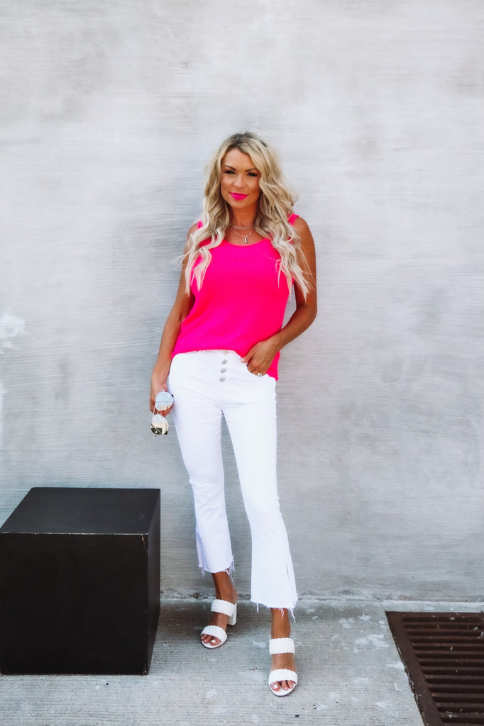 blonde woman wearing a neon pink tank and white cropped pants from A-List Boutique