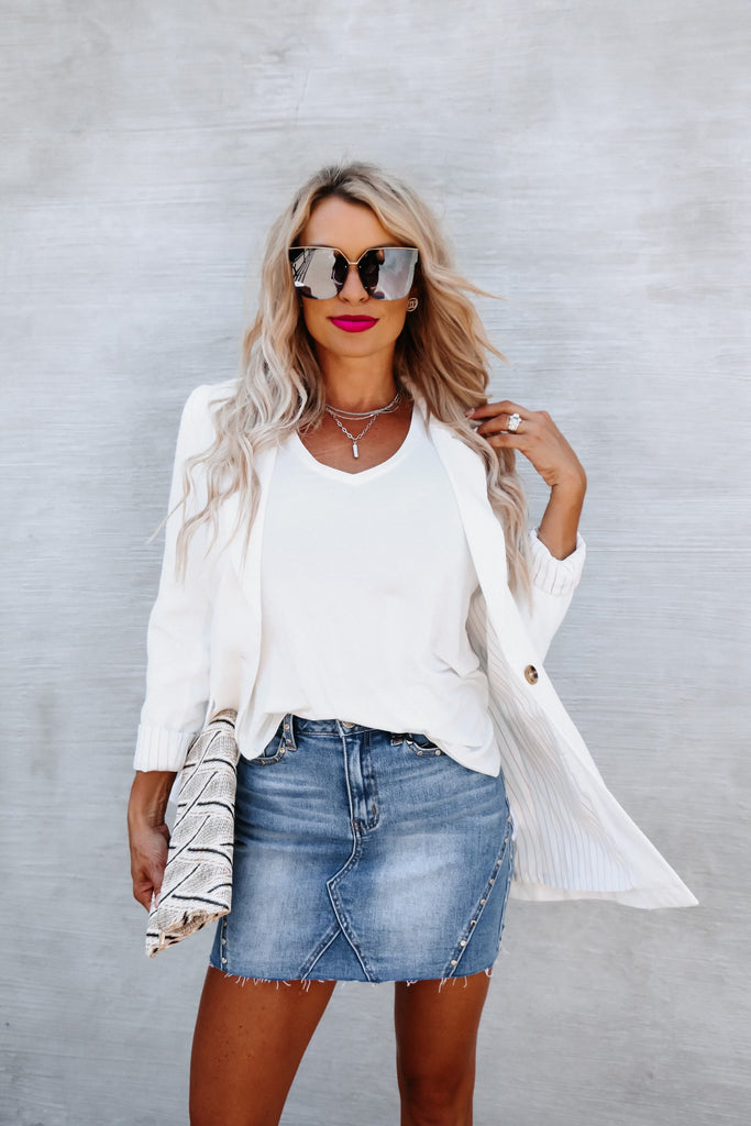 blonde woman in large black sunglasses posing in a white cardigan over a white t-shirt and jean skirt holding a faux-leather clutch purse