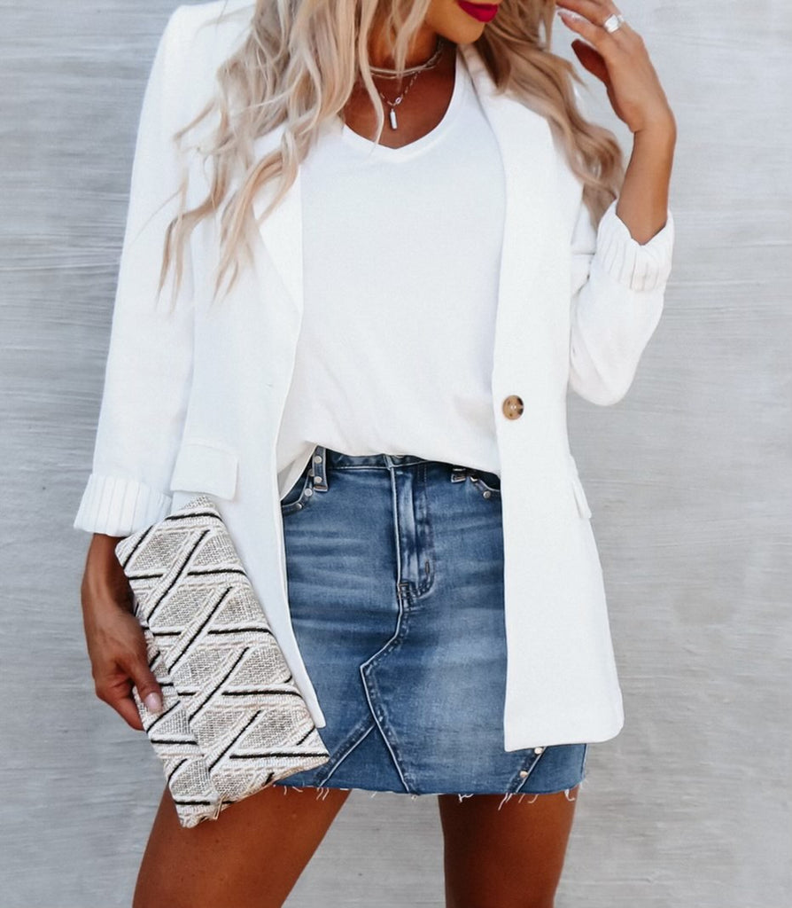 mid-section shot of blonde woman wearing a white cardigan over a t-shirt and a jean skirt, holding a white diamond textured clutch