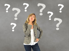 Woman looking confused with question marks around her on a grey background