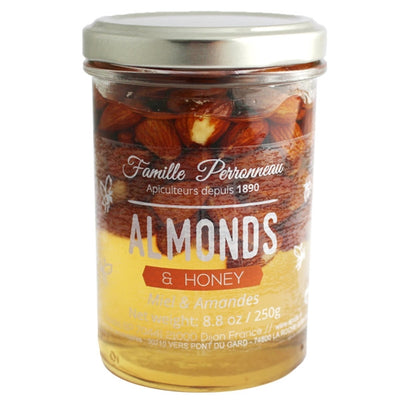 A glass jar with silver twist off lid filled with honey and almonds