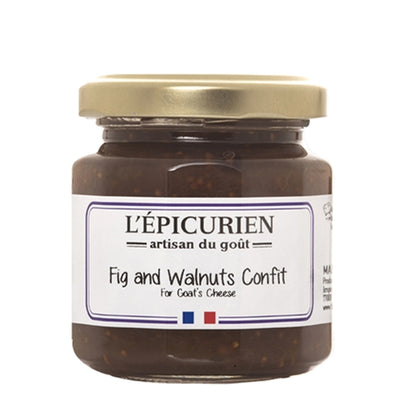 A small glass jar with a gold screw top lid with a white backdrop. The front label reads L'epicurien Fig and Walnuts Confit