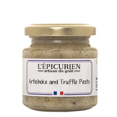 A small glass jar with a gold screw top lid with a white backdrop. The front label reads L'epicurien Artichoke and truffle pesto
