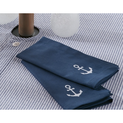Two blue napkins with white embroidery of an anchor lay folded on an outdoor table