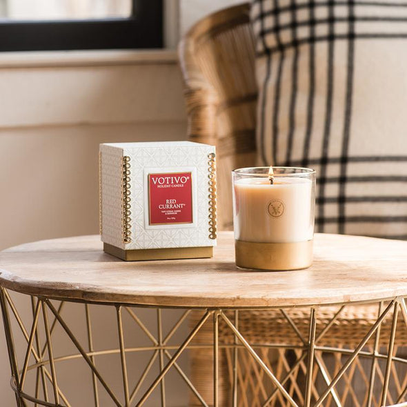 Square box with a red label saying votivo Red Currant Holiday candle.  Along side it is a glass candle with a gold bottom. both items sit on top an end table.