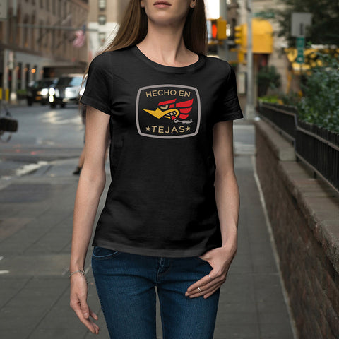 black, navy or charcoal gray options on relaxed fit ladies 100% cotton t shirt. charcoal grey has some polyester. crew neck and short sleeve women's fit tee. design is a pop graphic eagle with cigar in its teeth, based off of a rat rod look design. Image is in a rounded box with the words Hecho en Tejas meaning Made in Texas.