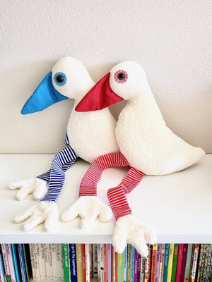 Photo of Esthex Sam Duck Blue and Red baby plushies sitting on top of a white bookcase with legs outstretched