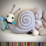 Front view of Esthex Simon Snail with Musicbox soft toy with gray shell and white ribbon swirl, polka-dotta dark blue scarf with bright blue fringe, white soft head with plaid antennae, sitting on top of white bookcase with other plushies