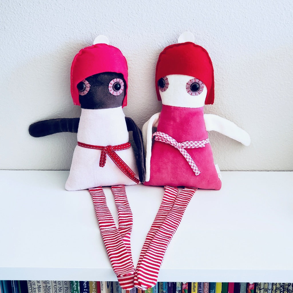Front view of Esthex Naomie & Sofie Plush Dolls sitting next to each other with outstretched arms and legs on top of white book case
