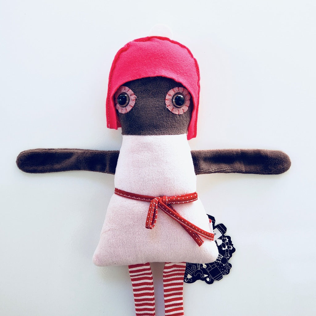 photo of upper half of Esthex Naomi plush doll with dark pink hat and light pink dress with red ribbon wrapped around the waist, red and white striped ribbon legs, and soft brown tone