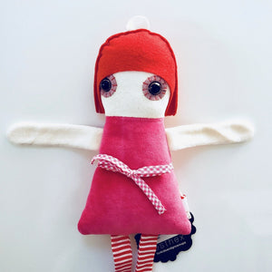 Overhead view of upper half of Esthex Sofie Plush Doll with red hat, dark pink body with checkered ribbon around waist, red & white striped ribbon legs and soft white tone
