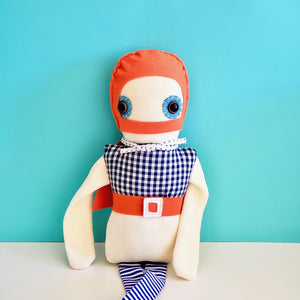 Esthex Storm Boy Plush Doll closeup view of upper body against a light blue background on top of white book case