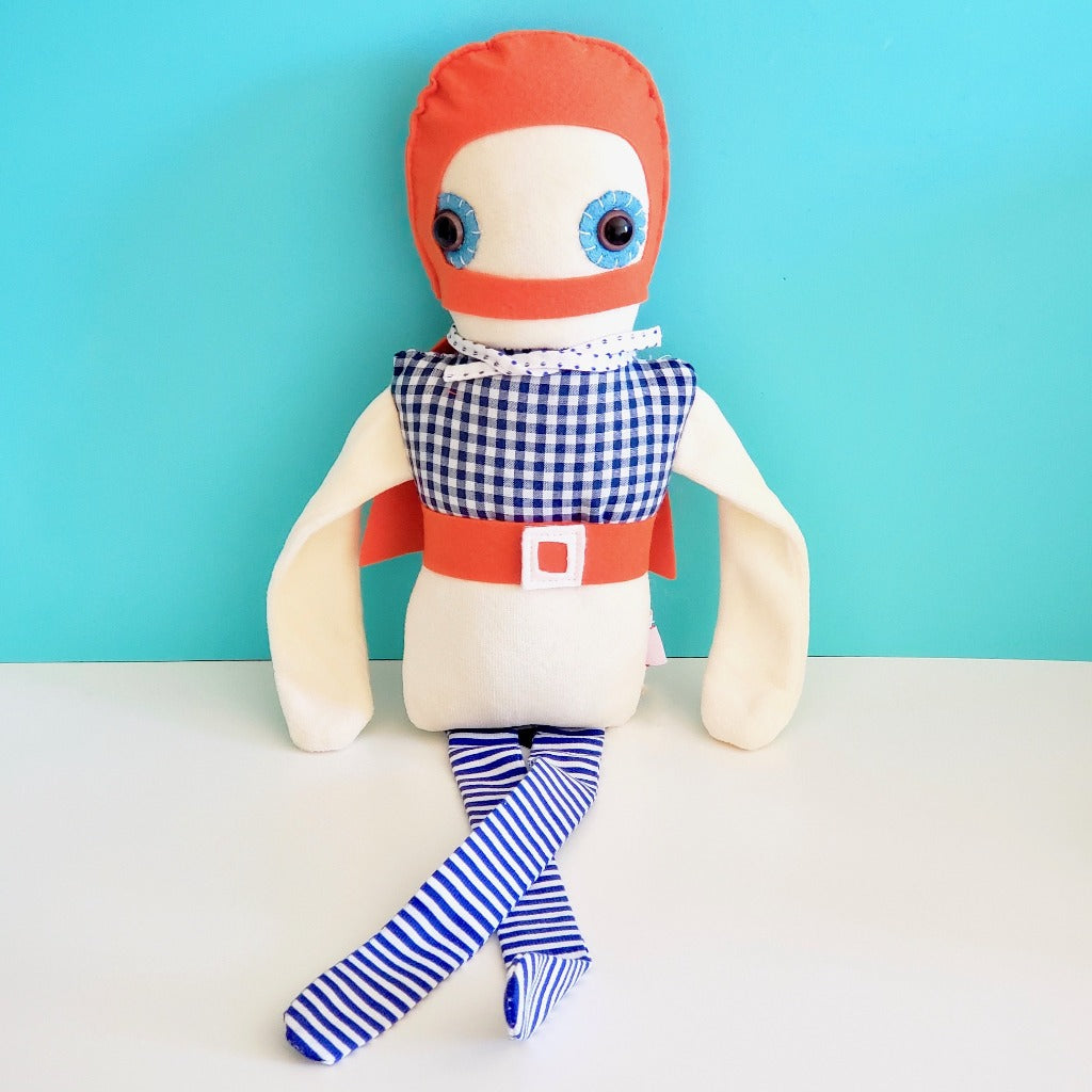 Front view of Esthex Storm Boy Plush Doll with orange mask and belt, checkered top half of body, blue and white striped ribbon legs, and cream colored body, sitting on top of white book case with light blue background