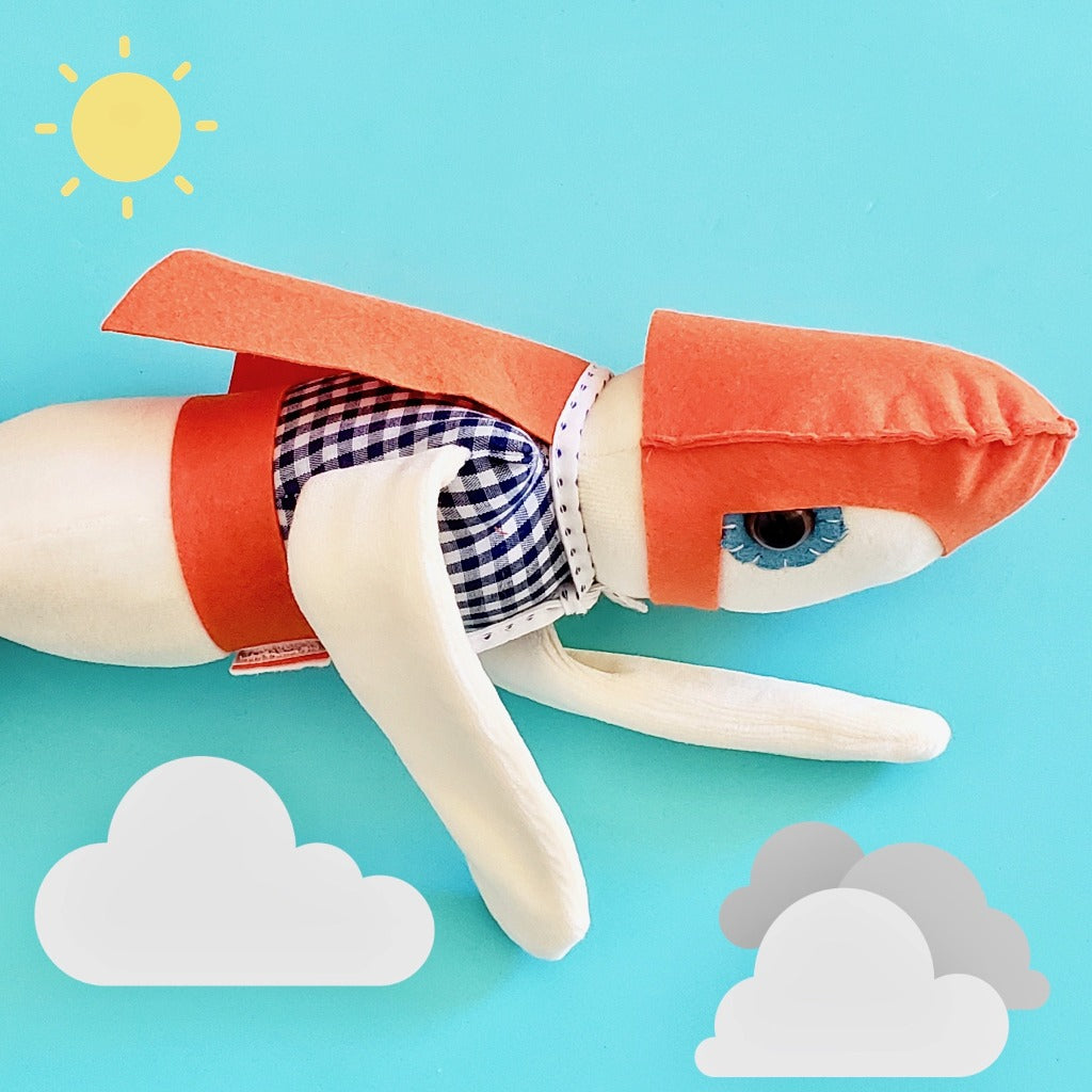 Esthex Storm Boy Plush Doll flying through light blue sky with cartoon images of the sun and clouds, with orange mask and cape