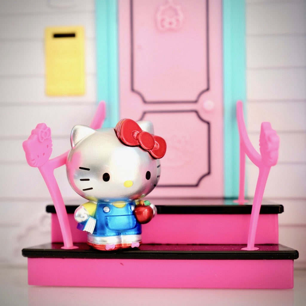 unboxed classic Hello Kitty Metalfigs on stairs in front of Hello Kitty Dollhouse