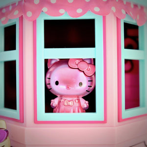unboxed all-pink Hello Kitty Metalfigs inside window of Hello Kitty dollhouse