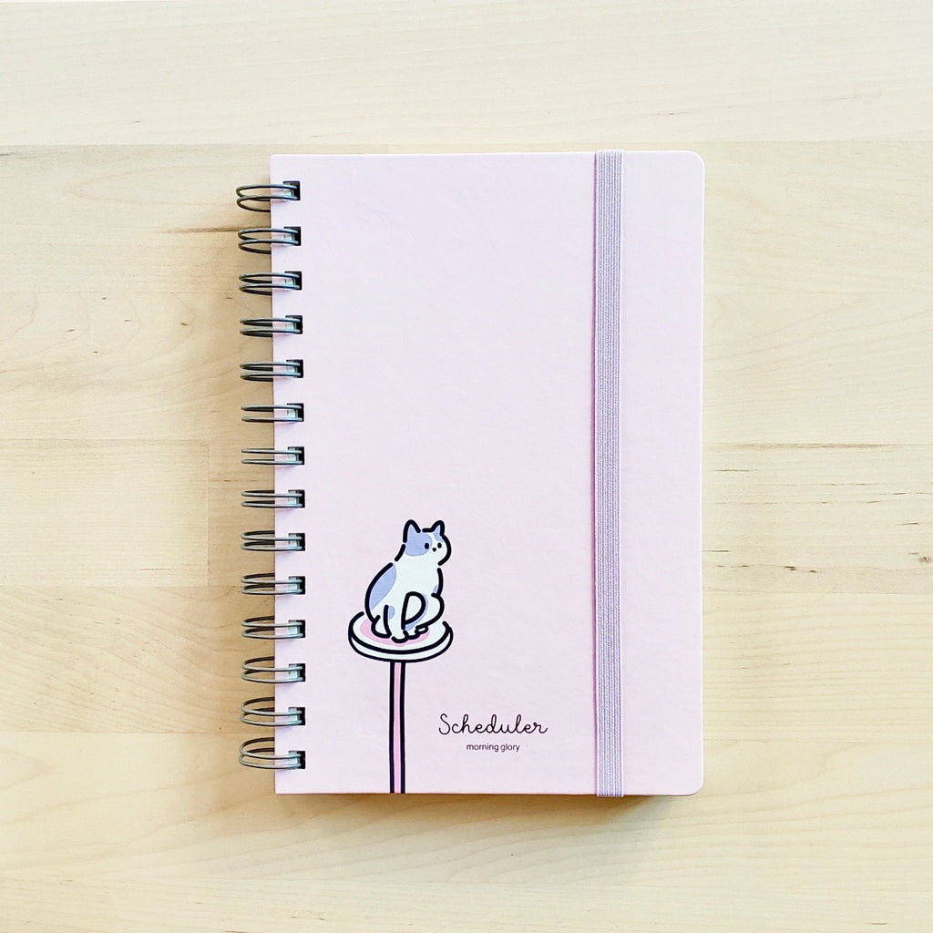 front cover of light pink morning glory scheduler with cat perched on cat tower